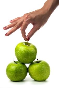 Kobieta ręka trzyma zielone jabłka na białym tle.
