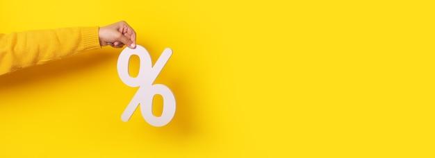 Kobieta ręka trzyma znak procentu biały 3d na żółtym tle, makieta panoramiczna