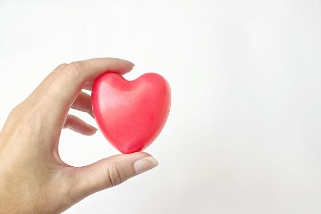 Kobieta ręka trzymać czerwone serce na białym tle. ubezpieczenie zdrowotne, darowizna, koncepcja ratowania życia