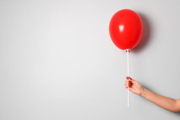 Kobieta ręka trzymać jeden czerwony balon ir w dłoni na szarym tle z bliska