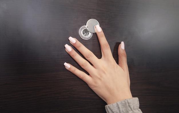 Kobieta ręka trzymać wizjer drzwi drewnianych.