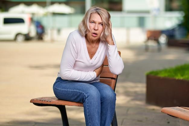 Kobieta ręka w ból brzucha na ulicy.