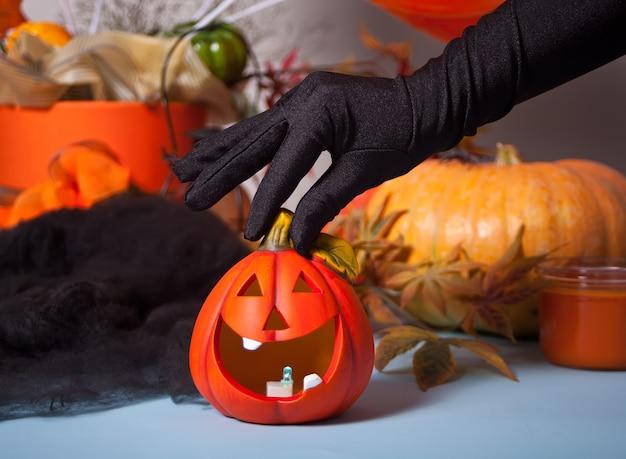 Kobieta ręka w czarnych rękawiczkach czarownicy trzyma latarnię jack dyni. koncepcja halloween.