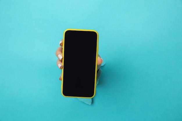 Kobieta ręka w niebieski papier otwór trzymając smartfon