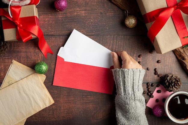 Kobieta ręka wkłada kartkę z życzeniami do koperty