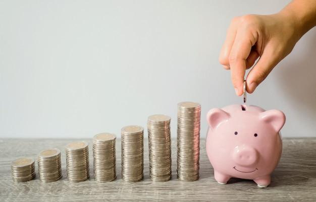 Kobieta ręka wkłada monetę do różowej skarbonki ze stosem monet, oszczędzając pieniądze fundusz emerytalny