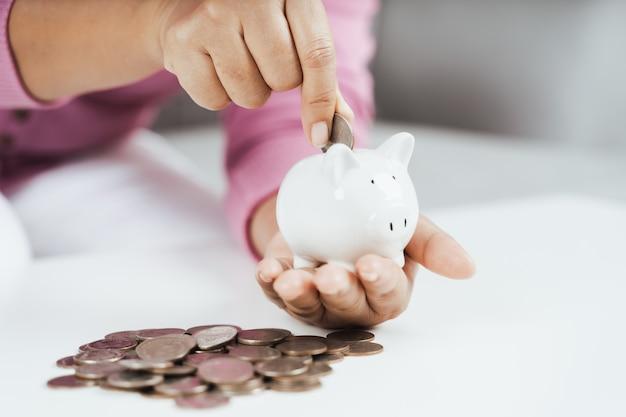 Kobieta ręka wkłada monetę do skarbonki, aby zaoszczędzić pieniądze, oszczędzając pieniądze i finanse
