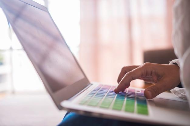 Kobieta ręka z bliska kaukaski ludzie pracują w domu z laptopem siedząc na kanapie z oświetleniem okna na powierzchni. kolorowa klawiatura i maszyna do pisania z jednym palcem