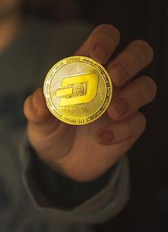 Kobieta ręka z dash krypto monetą, giełdą kryptowalut i zdjęciem koncepcji inwestycji