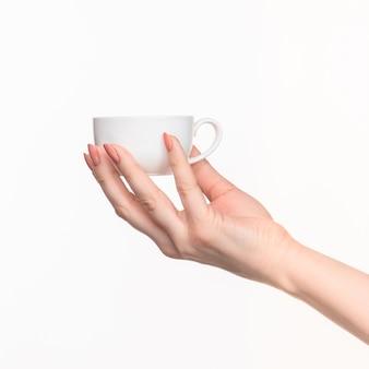 Kobieta ręka z doskonałym białym kubkiem na białym tle