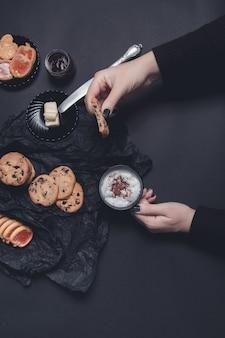 Kobieta ręka z filiżanką kawy lub cappuccino i ciasteczka czekoladowe, ciastka na tle czarny stół. przerwa popołudniowa. śniadanie.