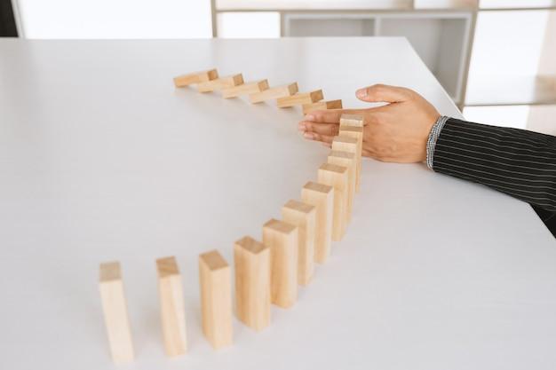 Kobieta ręka zatrzymuje drewniane klocki dla ochrony innego bloku koncepcja ryzyko zarządzania i planu strategicznego