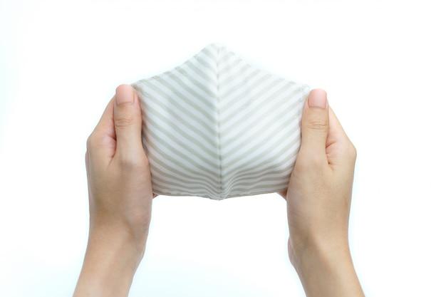 Kobieta ręki trzymającej maseczka z tkaniny lub ochronna maska raspiratory do rozprzestrzeniania wirusa