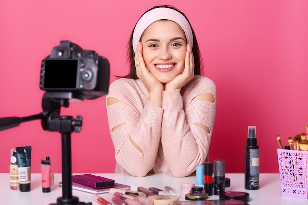 Kobieta reklamuje nowe produkty kosmetyczne, robi wideo swoim blogiem. piękno vlogger siedzi uśmiechając się przed kamerą
