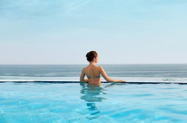 Kobieta relaks na skraju basenu bez krawędzi.