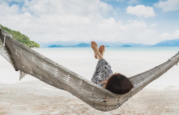 Kobieta relaks w hamaku z nogami na tropikalnej plaży na wakacjach.