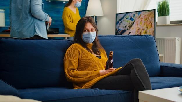 Kobieta relaksująca się z przyjaciółmi siedząca na kanapie w masce przeciw rozprzestrzenianiu się koronawirusa podczas globalnej pandemii trzymająca butelkę piwa patrząc na kamery. osoby towarzyskie podczas epidemii covid 19