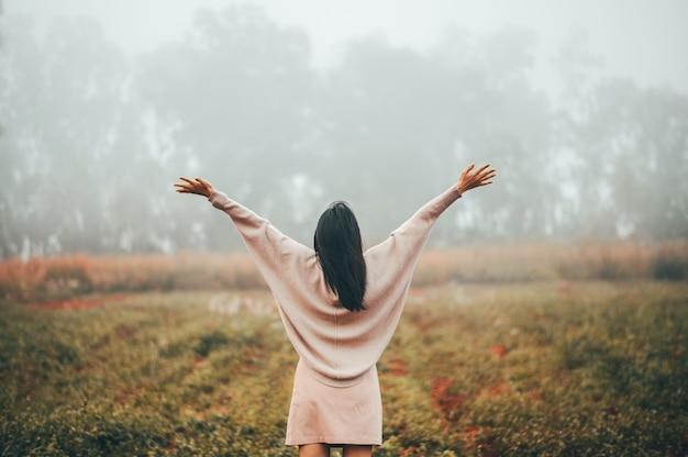 Kobieta relaksuje i cieszy się wolność w moring mgle