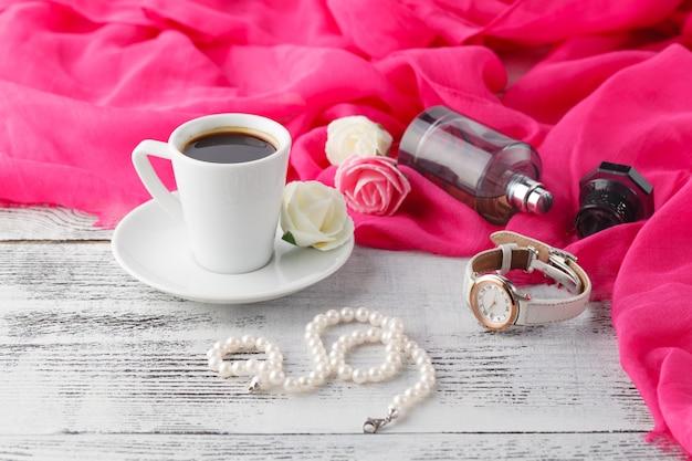 Kobieta relaksuje kawowego czas z szalem i parfum butelką na stole