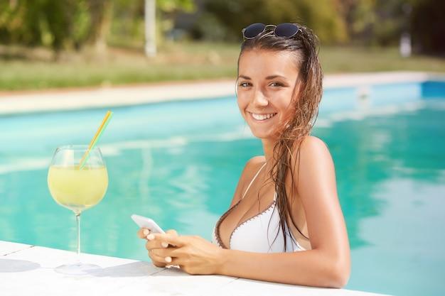Kobieta relaksuje koktajl przy pływackim basenem i pije