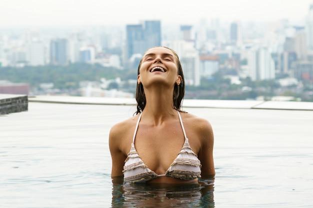 Kobieta relaksuje na dachu basenie