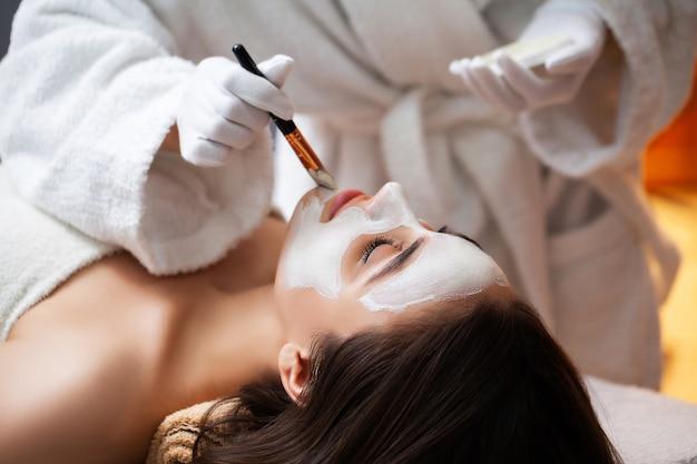 Kobieta relaksuje podczas zabiegów spa w salonie kosmetycznym