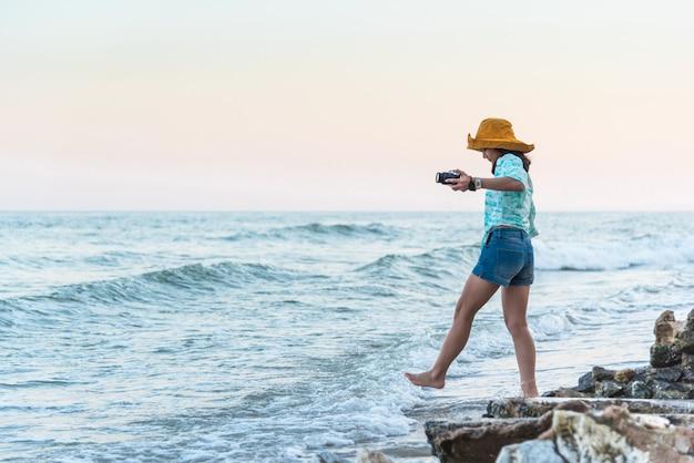 Kobieta relaksuje przy morze plażą w pojęcie podróży