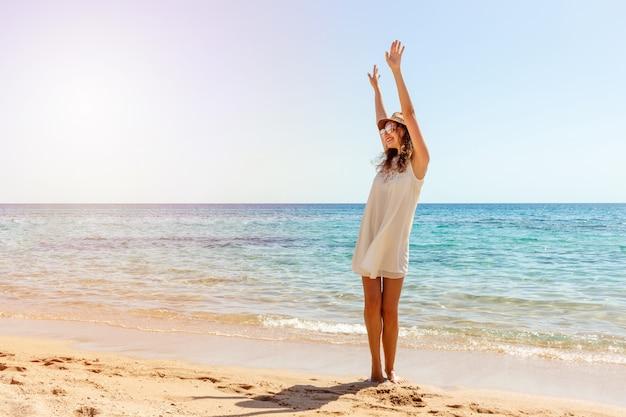 Kobieta relaksuje przy plażą cieszy się lato wolność. happ girl na plaży