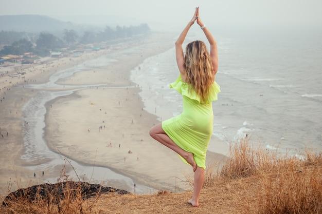 Kobieta relaksuje się na szczycie góry z widokiem na plażę