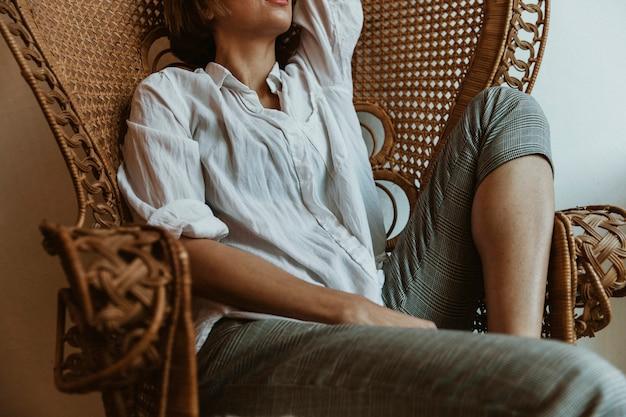 Kobieta relaksuje się na vintage wiklinowym krześle