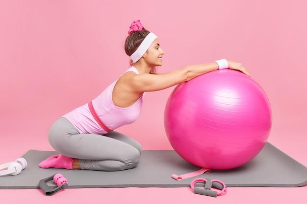 Kobieta relaksuje się po treningu pozuje na kolanach przy karemacie, pochyla się na dmuchanej piłce fitness, ubrana w strój sportowy