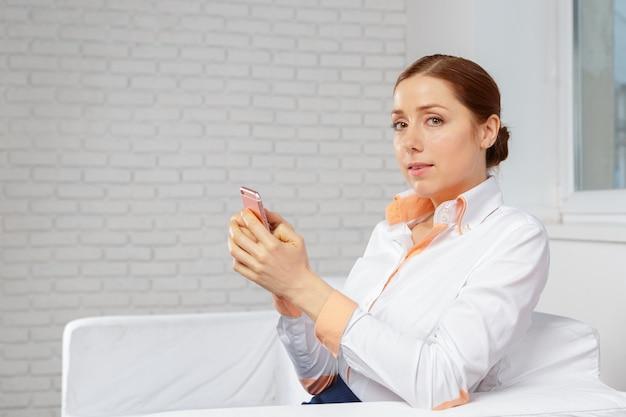 Kobieta relaksuje w kanapie opowiada na telefonie komórkowym