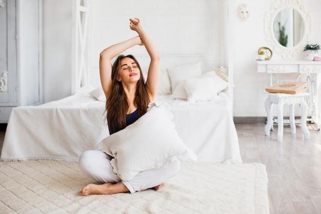 Kobieta relaksuje w łóżku i trzyma poduszkę