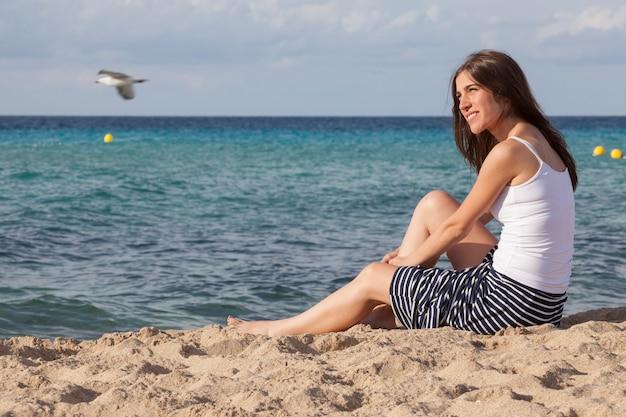 Kobieta relaksuje z zapierającym dech w piersiach widokiem na morze