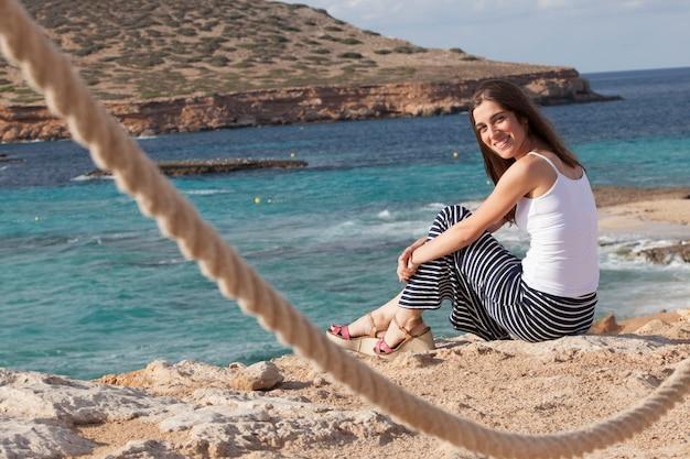 Kobieta relaksuje z zapierającym dech w piersiach widokiem plaży w ibiza