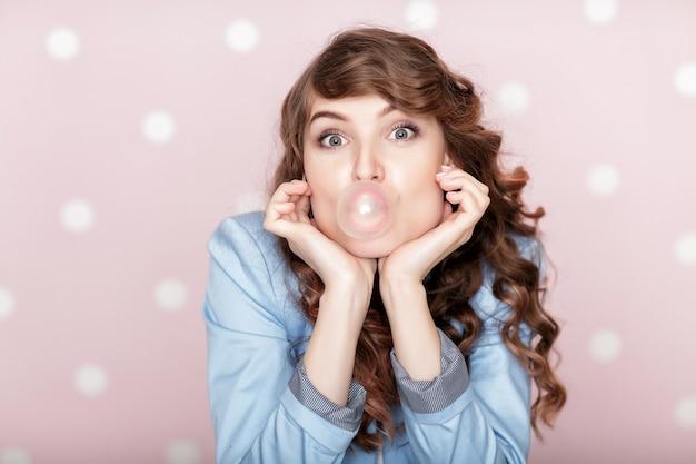 Kobieta robi bańki z gumą do żucia