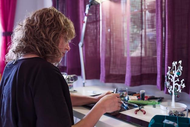 Kobieta robi biżuterię z gliny polimerowej