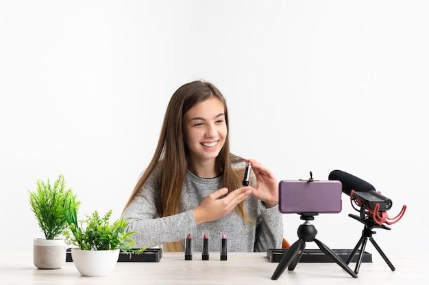 Kobieta robi blog z poradnikiem makijażu kosmetycznego z farbami do makijażu, patrząc na kamerę, udostępniając je w mediach społecznościowych na żywo w internecie
