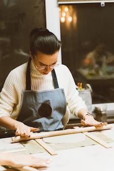 Kobieta robi ceramicznemu garncarstwu na warsztacie. pojęcie dla kobiety w freelance, biznes. rzemiosło