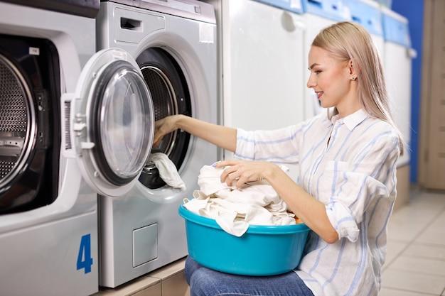 Kobieta robi codzienne obowiązki - pranie. kobieta złożone czyste ubrania w koszu na bieliznę, widok z boku. czyszczenie, koncepcja mycia
