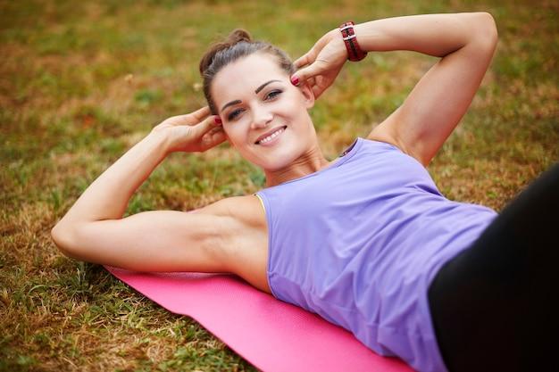 Kobieta robi ćwiczenia brzuszków w parku miejskim