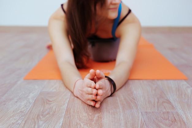 Kobieta robi ćwiczenia jogi na pomarańczowej macie, rozciąganie.