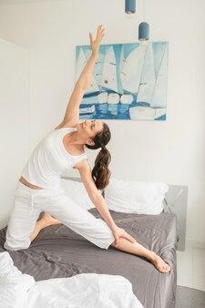 Kobieta robi ćwiczenia jogi w łóżku