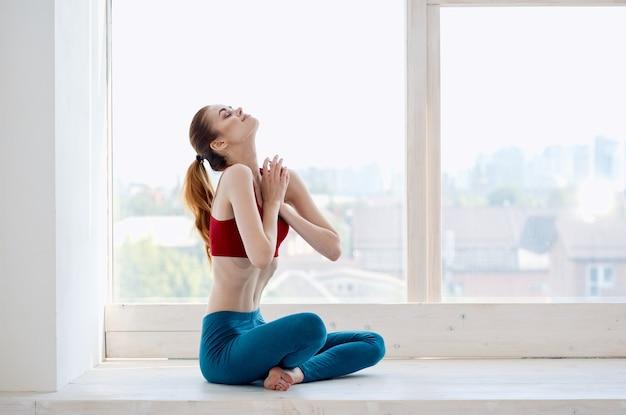 Kobieta robi ćwiczenia jogi w pobliżu asany energetycznej okna