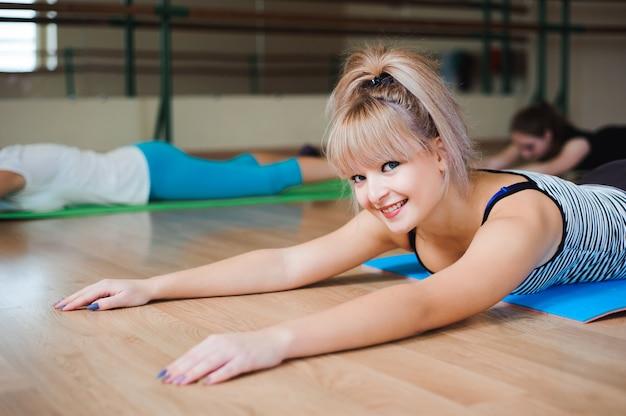 Kobieta robi ćwiczenia jogi w siłowni, sport fitness girl training stretching studio.