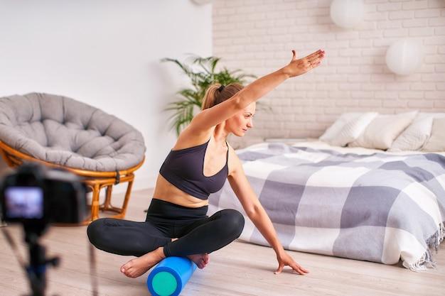 Kobieta robi ćwiczenia na specjalnym balansem symulatora. blond sportowa odzież sportowa, ćwiczenia domowe wzmacniają mięśnie.