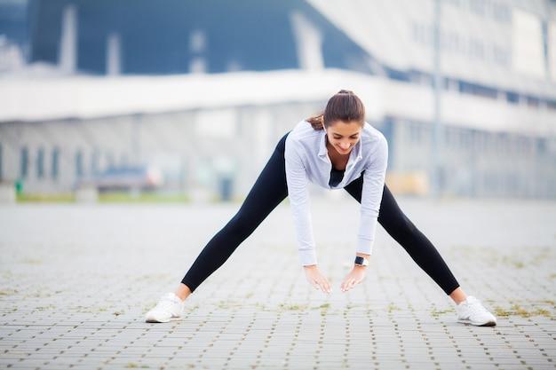 Kobieta robi ćwiczenia na ulicy