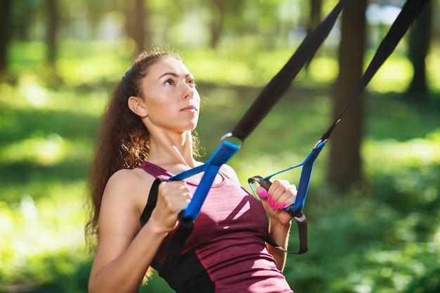 Kobieta robi ćwiczenia w parku na zawieszonym trenerze