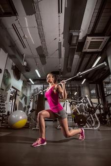 Kobieta robi ćwiczenia z barem wagi w siłowni.