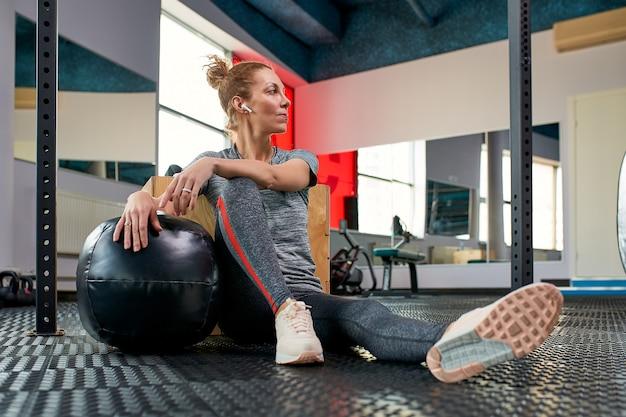 Kobieta robi ćwiczenia z fitball w klasie siłowni fitness. angażowanie mięśni brzucha. pojęcie wizerunku zdrowego stylu życia dla kobiet.